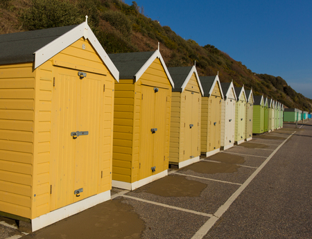 beach huts: Gold yellow and brown beach huts in a row with blue sky traditional English structure and shelter found at the seaside