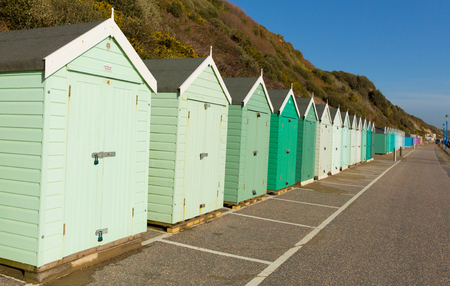 beach huts: Light green beach huts in a row with blue sky traditional English structure and shelter found at the seaside