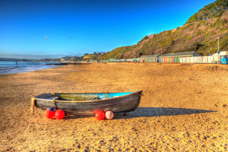 bright colour: Wooden rowing boat Bournemouth beach Dorset England UK like a painting in vivid bright colour HDR blue sky