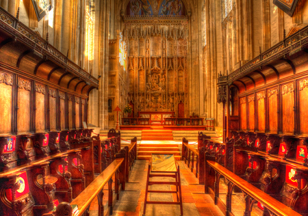 Church interior with rows of choir pews and steps leading up to the altar like painting in HDR