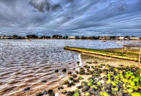 bright colour: Christchurch harbour near Mudeford Dorset England UK with rocks green seaweed boats and cloudscape like painting in vivid bright colour HDR