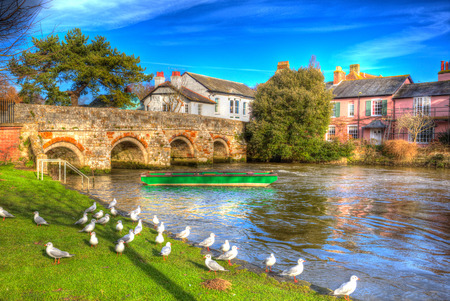 green boat: River Avon Christchurch Dorset England UK with bridge and green boat like a painting in vivid bright colourful HDR