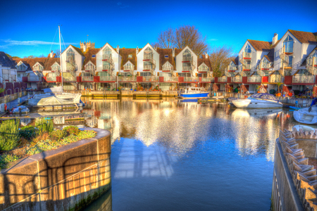 priory: Christchurch Priory Quay Dorset England UK exclusive marina development in vivid bright colour HDR wityh boats and reflections Stock Photo