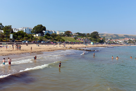 tourist destination: Swanage beach Dorset England UK with waves on the shore near Poole and Bournemouth at the eastern end of the Jurassic Coast a World Heritage Site popular south coast tourist destination