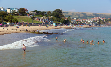 tourist destination: Swimming in the sea Swanage beach Dorset England UK near Poole and Bournemouth at the eastern end of the Jurassic Coast a World Heritage Site popular south coast tourist destination