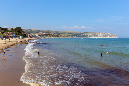 tourist destination: Bathers in the sea Swanage beach Dorset England UK with waves on the shore near Poole and Bournemouth at the eastern end of the Jurassic Coast a World Heritage Site popular south coast tourist destination