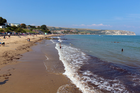 tourist destination: Swanage beach and coast Dorset England UK with waves on the shore near Poole and Bournemouth at the eastern end of the Jurassic Coast a World Heritage Site popular south coast tourist destination
