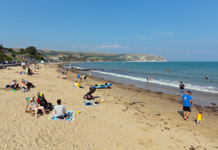 jurassic coast: Visitors in the summer sun Swanage beach Dorset England UK with waves on the shore near Poole and Bournemouth at the eastern end of the Jurassic Coast a World Heritage Site popular south coast tourist destination