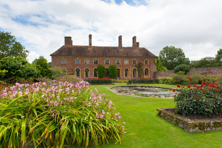 Strode House Barrington Court near Ilminster Somerset England uk with Lily pond garden and red dahlias