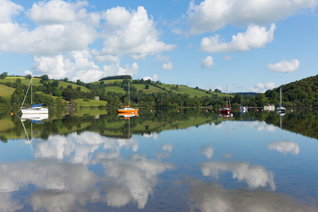 cumbria: The Lake District popular beautiful UK tourist destination Ullswater Cumbria North England in summer with boats blue sky and cloud reflections