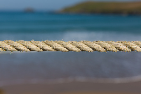 tight: Length of rope pulled tight against a blurred blue background of sea waves and coast Stock Photo