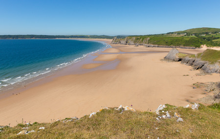 bristol channel: Sandy beach, The Gower Peninsula Pobbles beach Wales UK, popular tourist destination and next to Three Cliffs Bay in summer with blue sky and sea Stock Photo