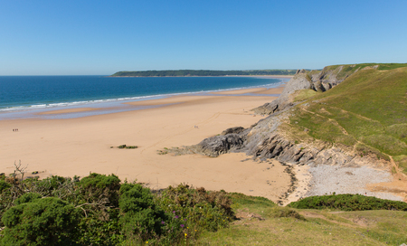cymru: Pobbles beach Gower Peninsula, Wales, uk. Popular tourist destination and next to Three Cliffs Bay in summer with blue sky and sea