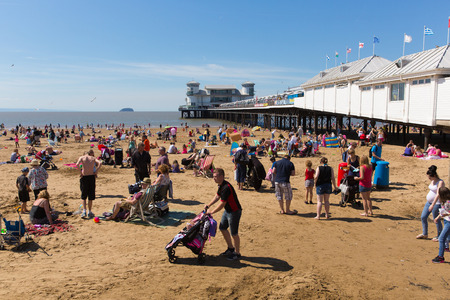 English summer scene beach at Weston-super-Mare Somerset with pier tourists and visitors enjoying the August sunhine