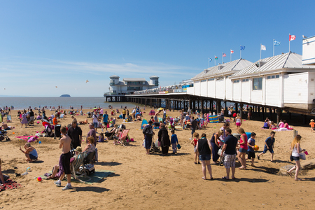 English summer scene Weston-super-Mare beach and pier Somerset with tourists and visitors enjoying the sun