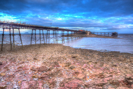 birnbeck: English Victorian pier Birnbeck island Weston-super-Mare Somerset England in colourful HDR with rock pools and rocks in foreground Stock Photo