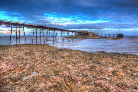 english west country: Birnbeck Pier Weston-super-Mare Somerset England in colourful HDR with rock pools and rocks in foreground