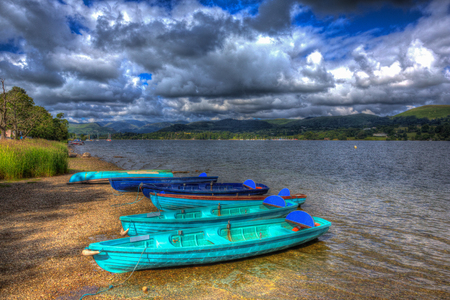 cumbria: Wooden rowing boats by a lake with mountains and blue sky Ullswater the Lake District Cumbria England UK in HDR like painting