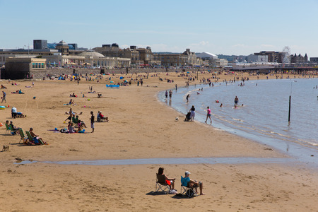 english west country: Weston-super-Mare beach Somerset uk with tourists and visitors enjoying the summer sun