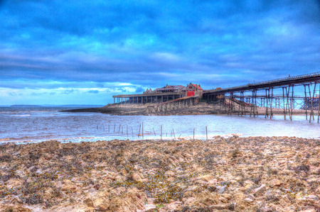 english west country: English Victorian pier Birnbeck island Weston-super-Mare Somerset England in colourful HDR with rock pools and rocks in foreground Stock Photo
