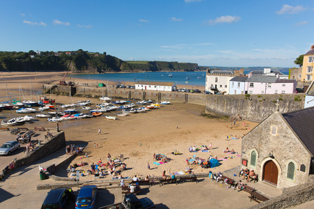 tenby wales: View from harbour Tenby South Wales uk in summer with tourists and visitors and blue sky