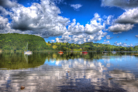 lake district england: Beautiful lake with boats and hills on a calm still summer day in Ullswater the Lake District England in colourful HDR Stock Photo