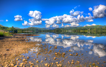 lake district england: White fluffy clouds reflecting on beautiful lake with mountains and water like glass on a calm still summer day in Ullswater the Lake District England in colourful HDR Stock Photo