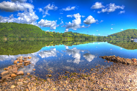 lake district england: Beautiful lake with cloud reflections on a calm still summer day in Ullswater the Lake District England in colourful HDR Stock Photo