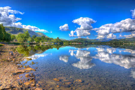 lake district england: UK Lake District England Ullswater with hills and mountains and clouds on beautiful still summer day with reflections Stock Photo
