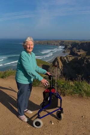 three wheel: Elderly lady pensioner with three wheel mobility aid walking frame by beautiful coast scene Stock Photo