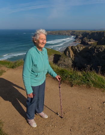 eighties: Elderly female pensioner in her eighties with walking stick by beautiful coast scene at Bedruthan Steps Cornwall England UK