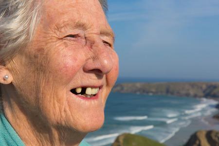 歯の問題と歯の美しい海岸の風景がなくなった高齢者女性の年金受給者