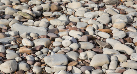 Grey pebbles and stones and shingle, a background texture found on the beach in St Audries Bay Somerset uk