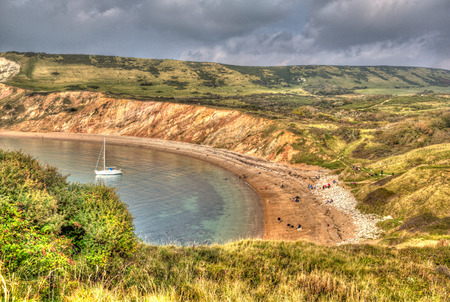Yacht in Worbarrow Bay east of Lulworth Cove on the Dorset coast England uk in colourful HDR
