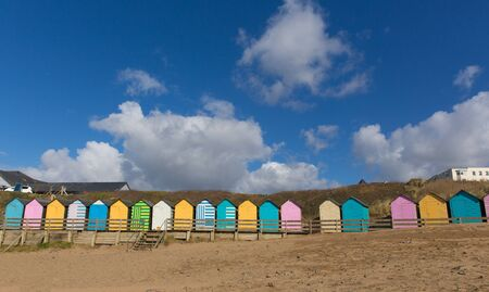 beach huts: Traditional colourful English seaside scene with beach huts on the beach and blue sky with pastel colours Stock Photo