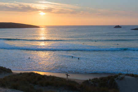 surfers: Surfers sunset in Cornwall surfing in evening Crantock bay and beach North Cornwall England UK near Newquay Stock Photo