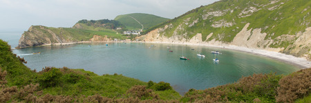 inlet bay: Lulworth Cove Dorset England uk with boats in the natural harbour top tourist attraction on English Jurassic Coast panoramic view Stock Photo