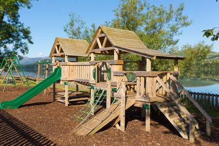 climbing frame: Wooden climbing frame for children in rural outdoor location by a lake