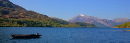 Loch Leven Lochaber Geopark Scotland uk view to Glen coe in Scottish Highlands with boat panorama Stock Photo