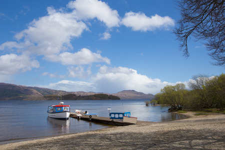Loch Lomond Scotland UK in summer with blue sky boat and jetty popular Scottish tourist destination Stock Photo