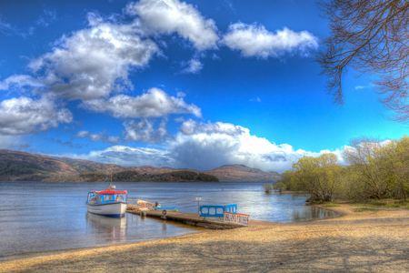 Loch Lomond Scotland UK in The Trossachs National Park with boat blue sky and clouds Stock Photo