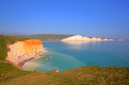 Beautiful UK coast Seven Sisters chalk cliffs East Sussex uk between Seaford and Eastbourne with sea lapping the rocks Фото со стока
