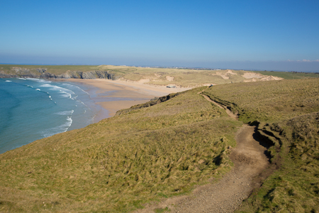 South west coast path Holywell bay North Cornwall with blue sea waves and sky