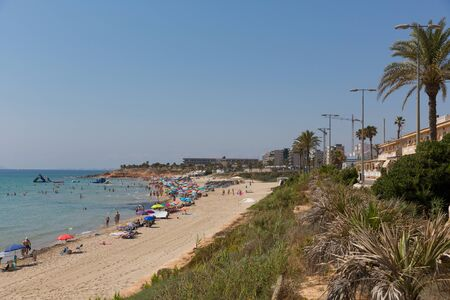 Mil Palmeras beach Costa Blanca Spain with palm trees and holidaymakers with parasols in beautiful summer weather