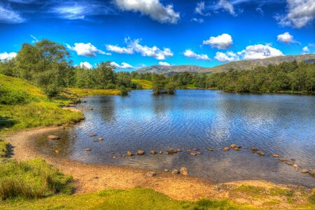 English Tarn Hows Lake District National Park uk near Hawkshead with trees in colourful HDR Stock Photo