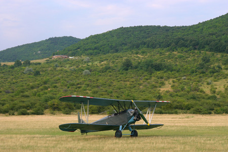 fuselage: Old-fashioned biplane landed   A vintage camouflage biplane secured to the ground at a grassy airfield