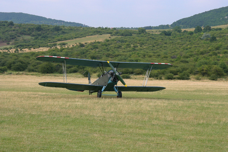 grassy: Old-fashioned biplane landed   A vintage camouflage biplane secured to the ground at a grassy airfield