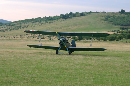 secured: Old-fashioned biplane landed  A vintage camouflage biplane secured to the ground at a grassy airfield