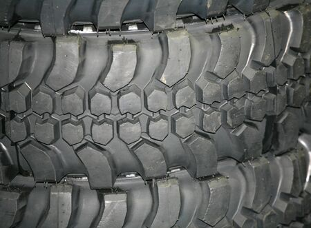 off track: Four wheel drive tire stack as a background. 4WD tyres.  Part of brand new car tyre. Tire Track Off R Stock Photo