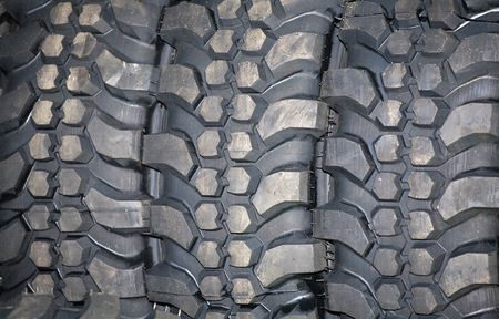 4wd: Four wheel drive tire stack as a background. 4WD tyres.  Part of brand new car tyre. Tire Track Off Road